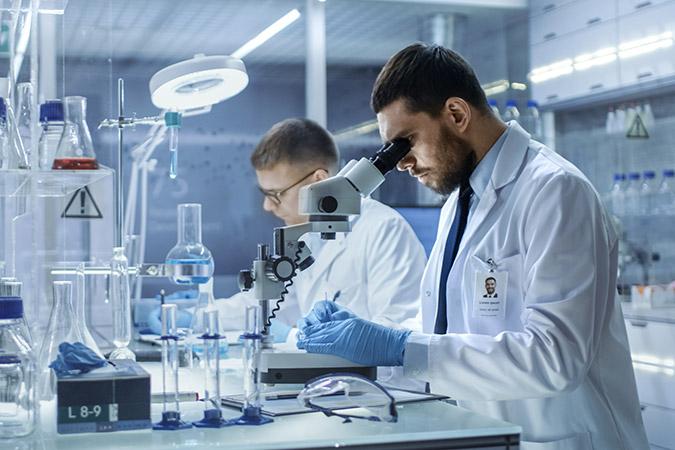 2 scientifiques hommes dans un laboratoire, travaillant grâce au don reçu pour la recherche et l'innovation par adrinord