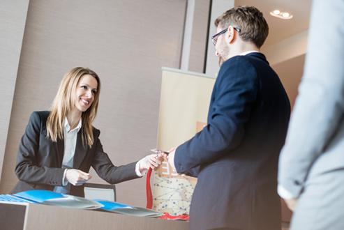 hôtesse remettant un badge lors d'un événement scientifique pour adrinord